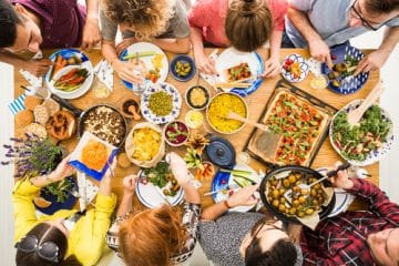 Gruppe von Menschen beim Essen von veganer Ernährung oder vegetarischer Ernährung.