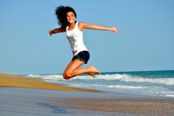Gesunder Lebensstil erfreut Frau am Meer und daher springt sie in die Luft.